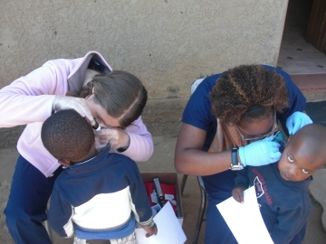 Liz and Kelli performing otoscopy outside the one of the Creche classroom. Great job bridging!
